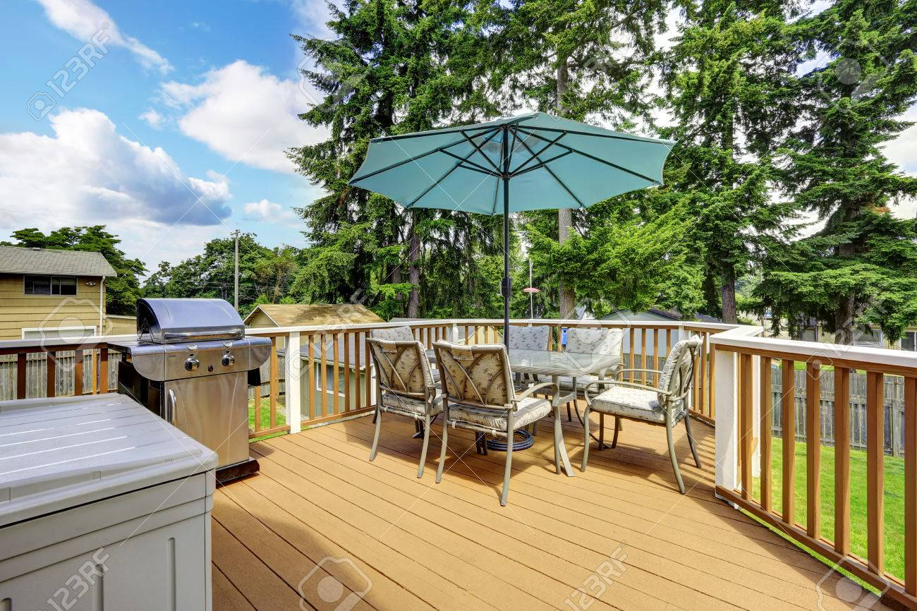 Stock Photo   Walkout Deck In Brown And White Trim. Patio Table Set With  Umbrella And Jacuzzi