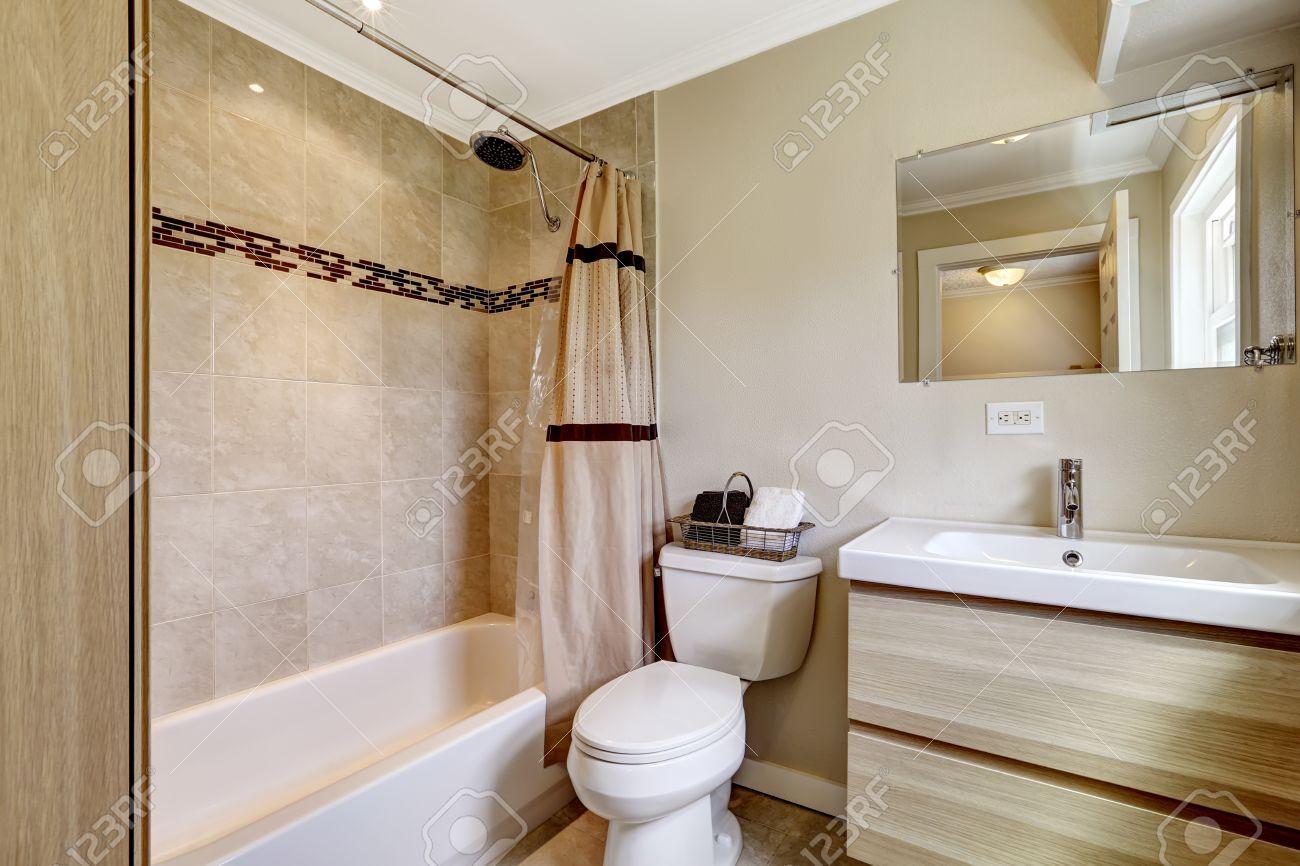 Cuarto de baño con adornos de azulejos de color beige y de cortina  melocotón. Armario moderno con lavabo en todo lo alto