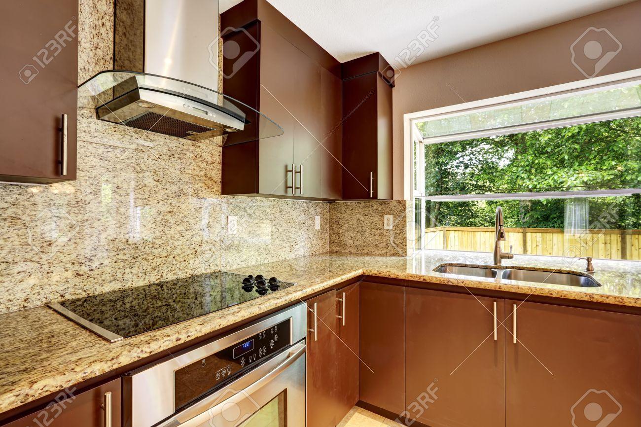 moderna sala de cocina con gabinetes mate marrn encimeras de granito brillante estufa de