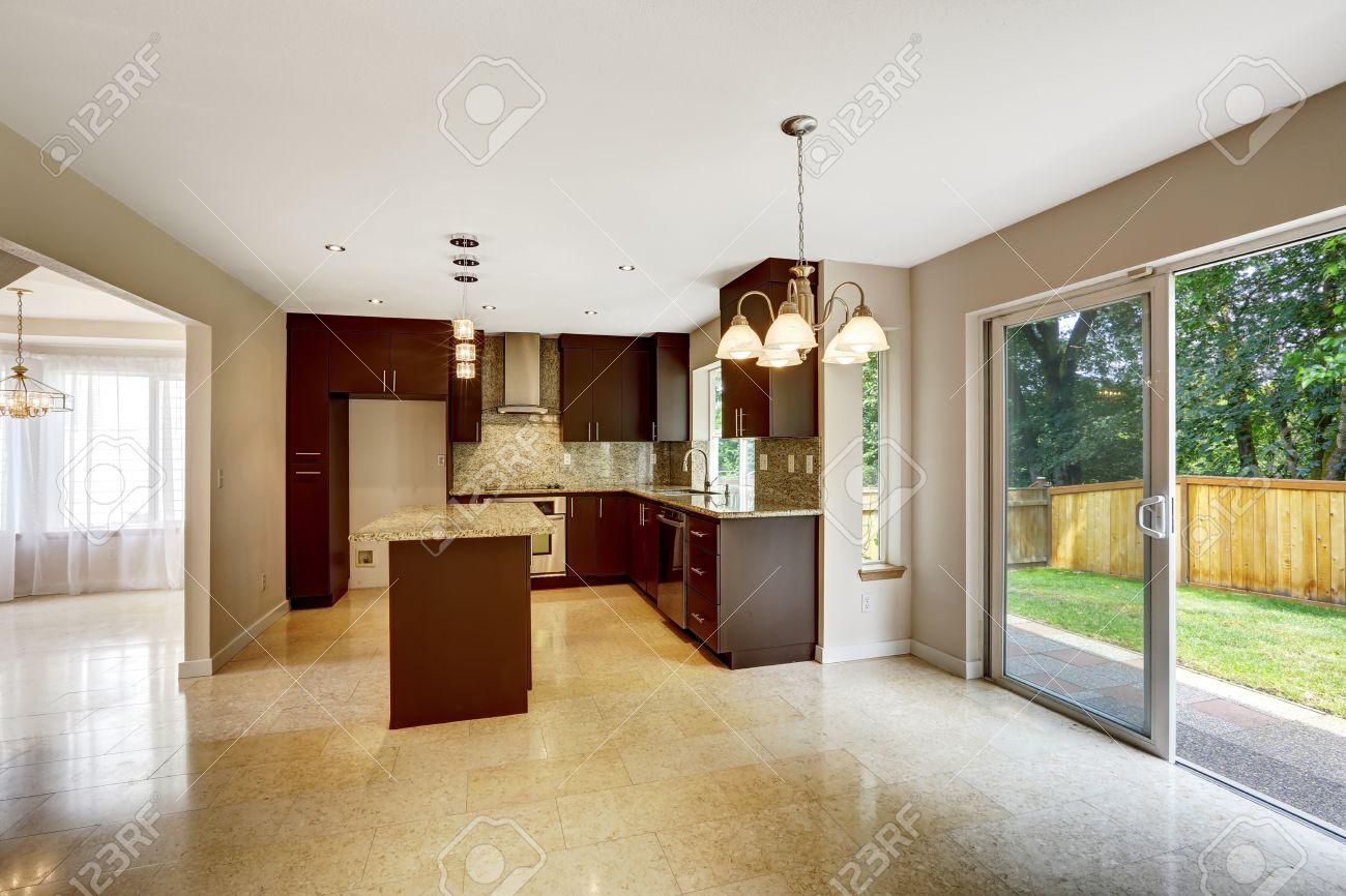 Salle de cuisine moderne avec armoires brun mat, en granit brillant. Maison  intérieur avec carrelage de marbel et la sortie à la cour