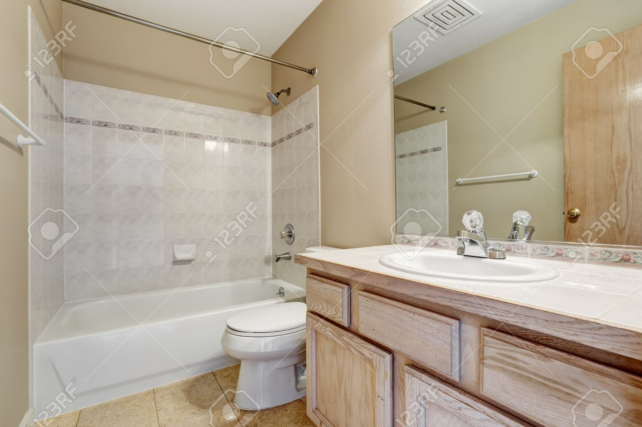 Warm Bathroom In Creamy Color With White Tile Wall Trim Stock Photo