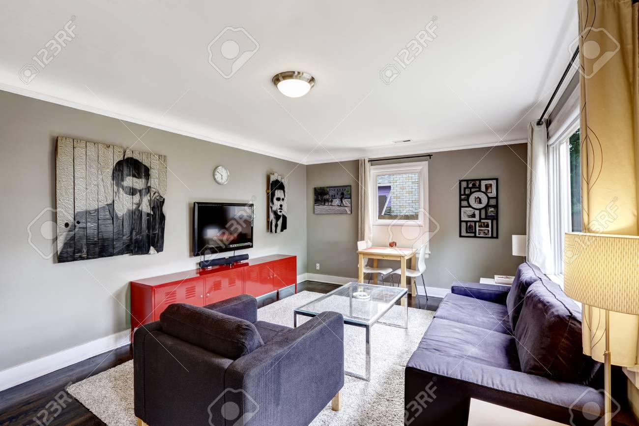 Hellgraues Wohnzimmer Mit Leuchtend Rotem Schrank. Schwarzes Sofa Und  Sessel Mit Couchtisch Aus Glas Standard