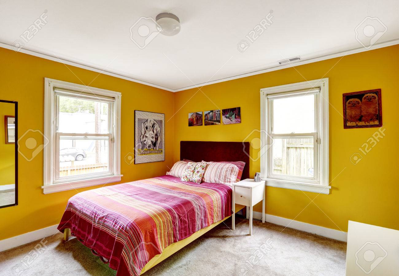 Bedroom In Bright Yellow Color With Single Bed Red Stripped Stock