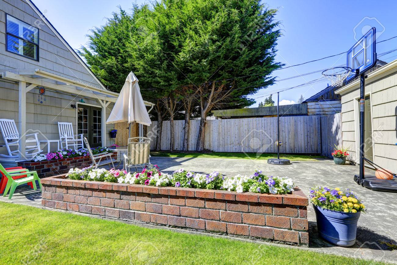 small backyard area with basketball court and brick flower bed