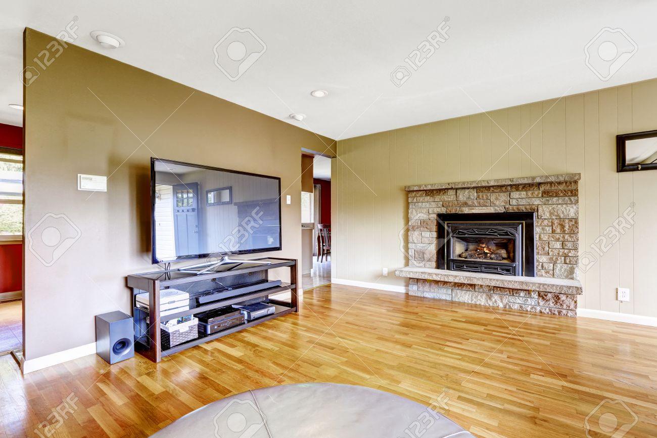 sala de estar con chimenea de piedra de corte y tv piso de madera y