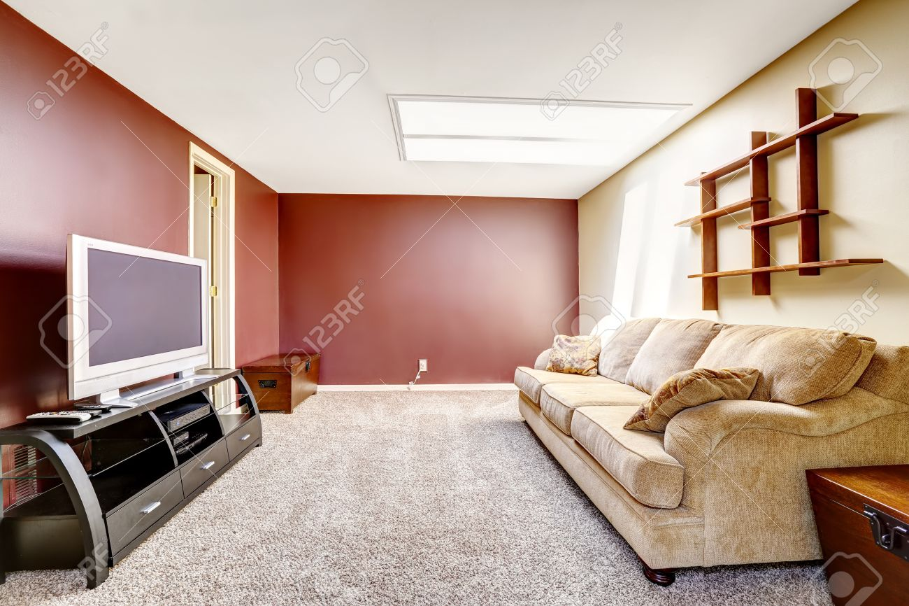 Bright living room with contrast red wall, comfortable sofa and..