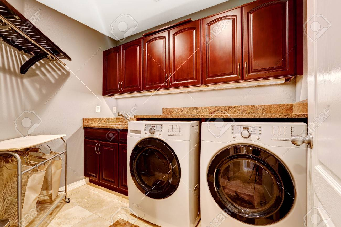 modern laundry room interior with whtie appliances and bright wooden cabinets with granite tops stock photo bright modern laundry room