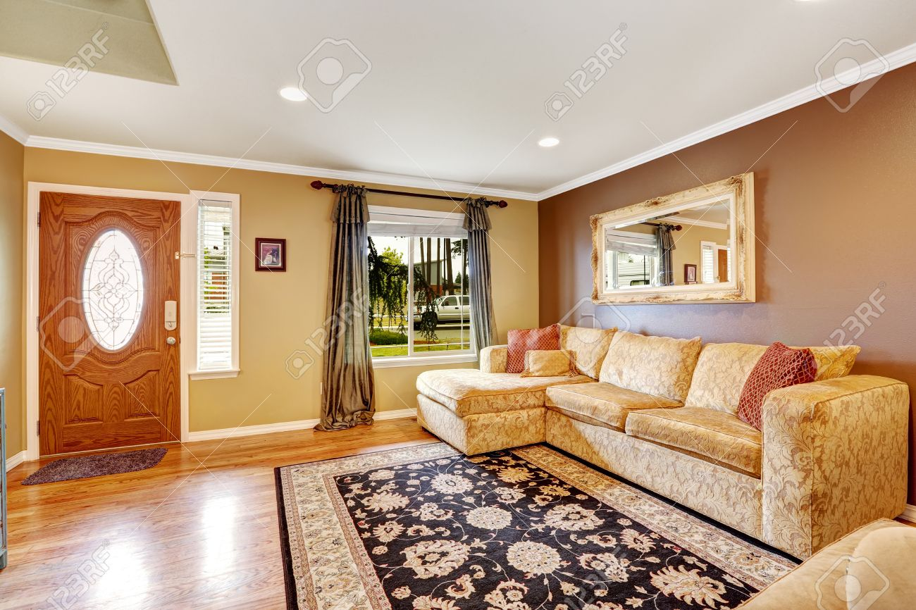 Living room with brown and ivory color walls. Creamy tone sofa..