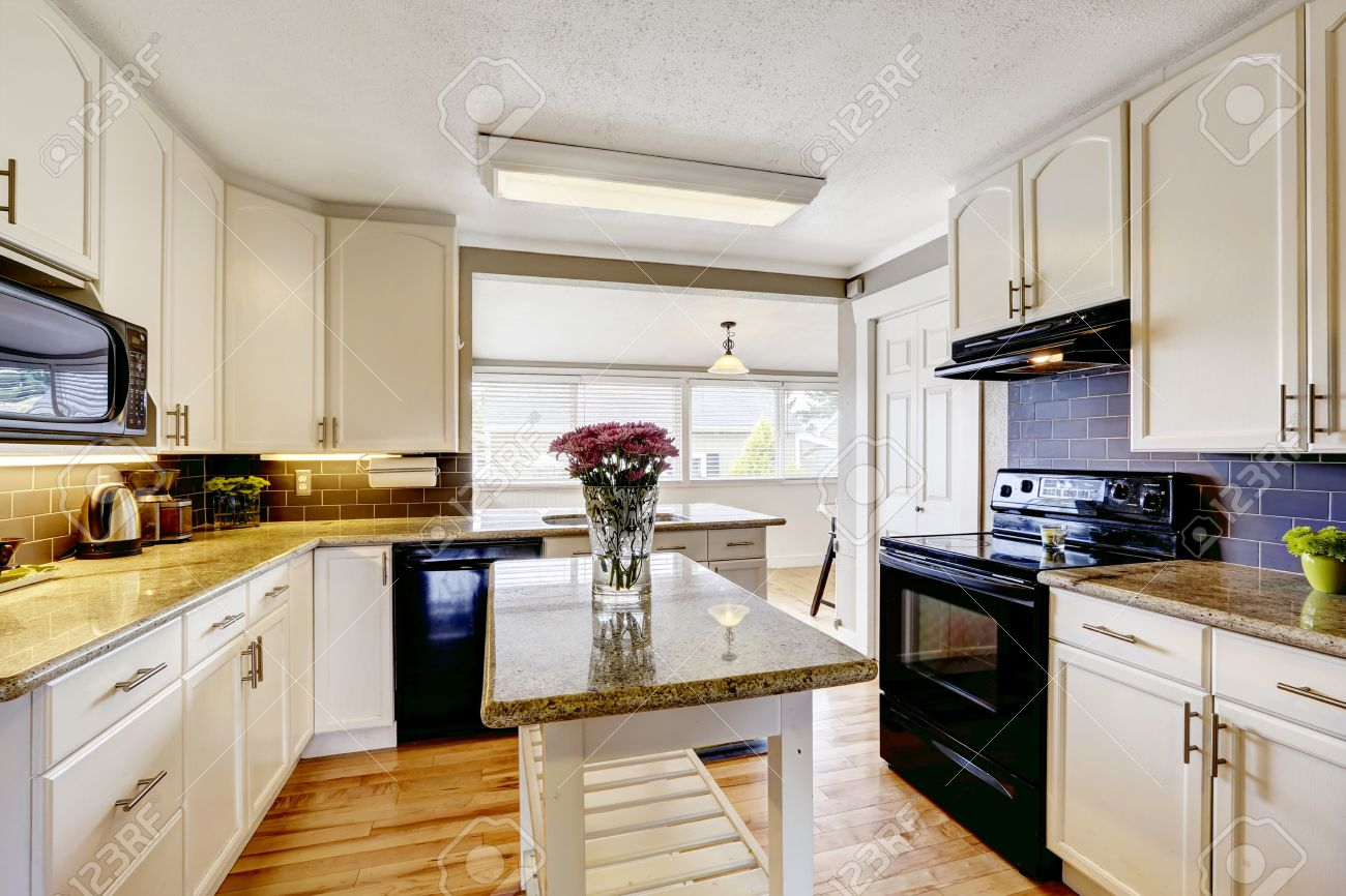 White Kitchen Cabinets With Black Appliances. Kitchen Island.. Stock ...