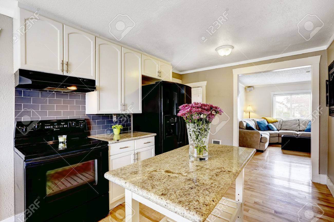 White Kitchen Cabinets With Black Appliances Island Granite Top Decorated Flowers Stock