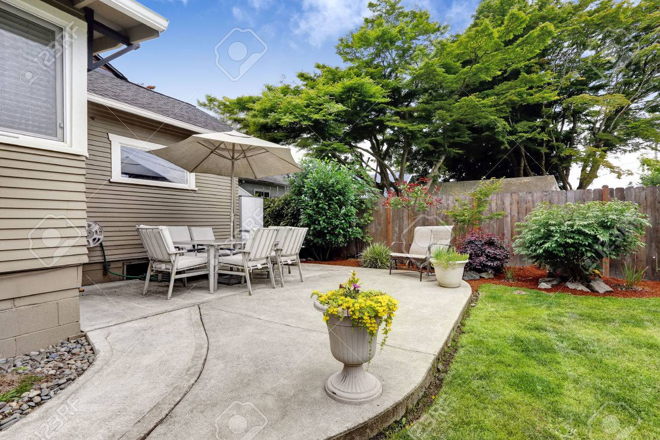 Backyard Patio Area With Table Set And Umbrella. Patio With Concrete Floor  And Flower Pots