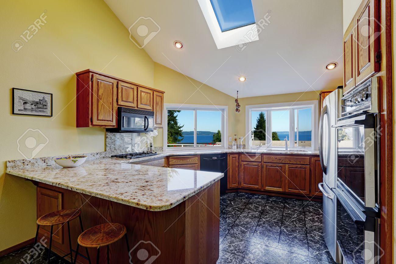 Foto de archivo hermosa cocina con techo alto y abovedado tragaluz suelo de baldosas de granito negro la habitación tiene increíble vista a la bahía