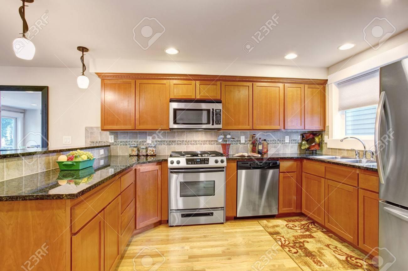 Esdoorn keuken kasten met stalen apparatuur en granieten toppen ...