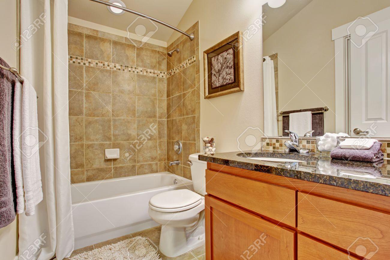 Badrum interiör. maple skåp med granitskiva och spegel. vit badkar ...
