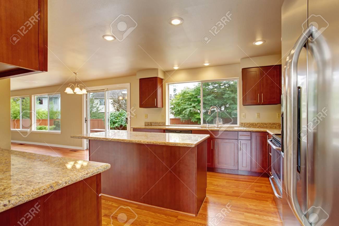 Cucina con armadi in legno chiaro, frigorifero in acciaio. Camera Cucina è  uscita al cortile