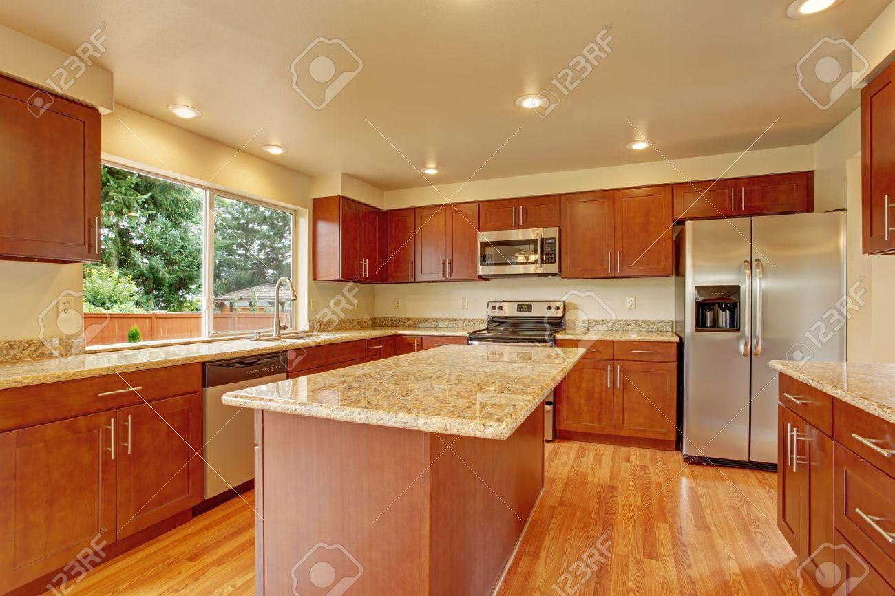 Cucina con mobili in legno chiaro, elettrodomestici in acciaio e top in  granito. Camera Cucina è dotata di cucina ad isola