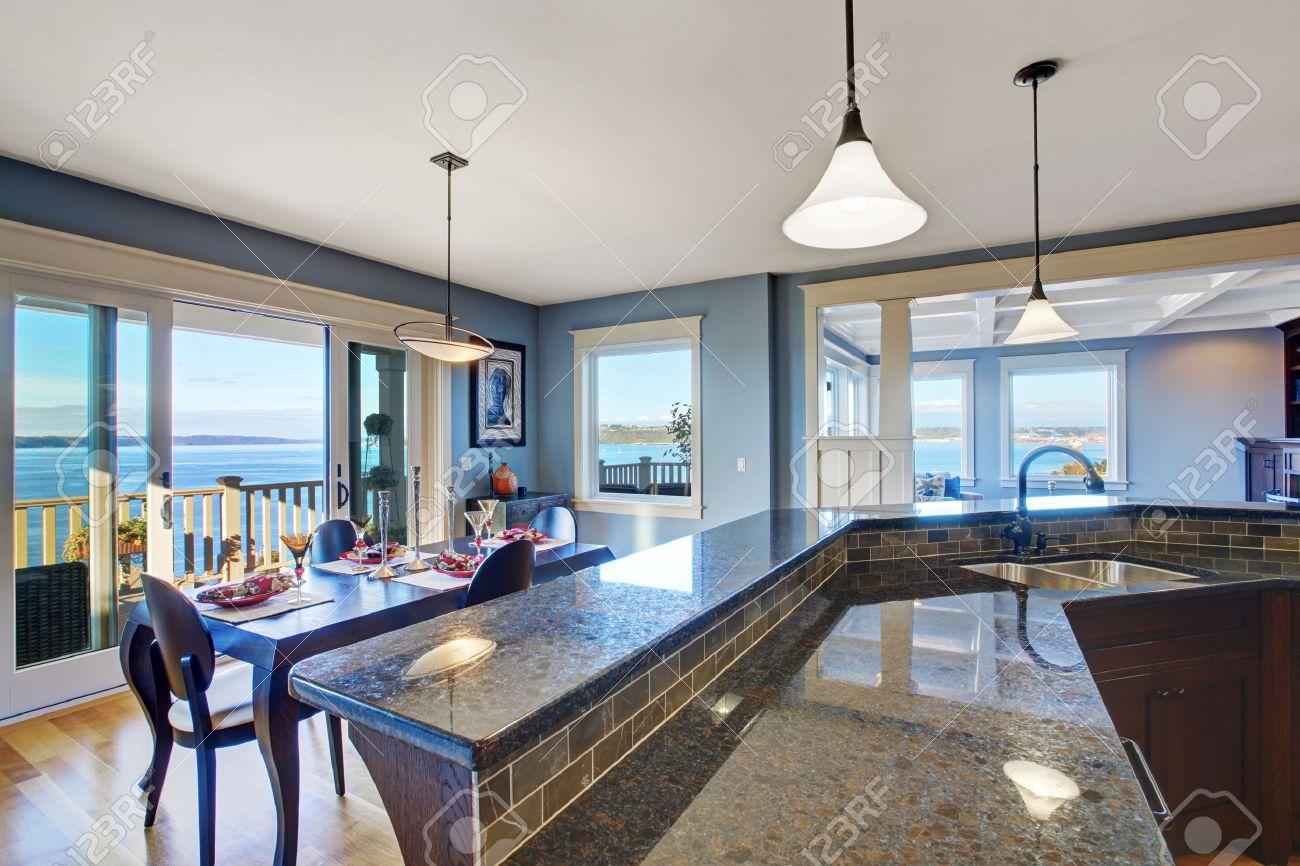 Cucina di lusso con mobili marrone scuro e top in granito. Cucina è dotata  di zona pranzo e porte scorrevoli a ponte sciopero