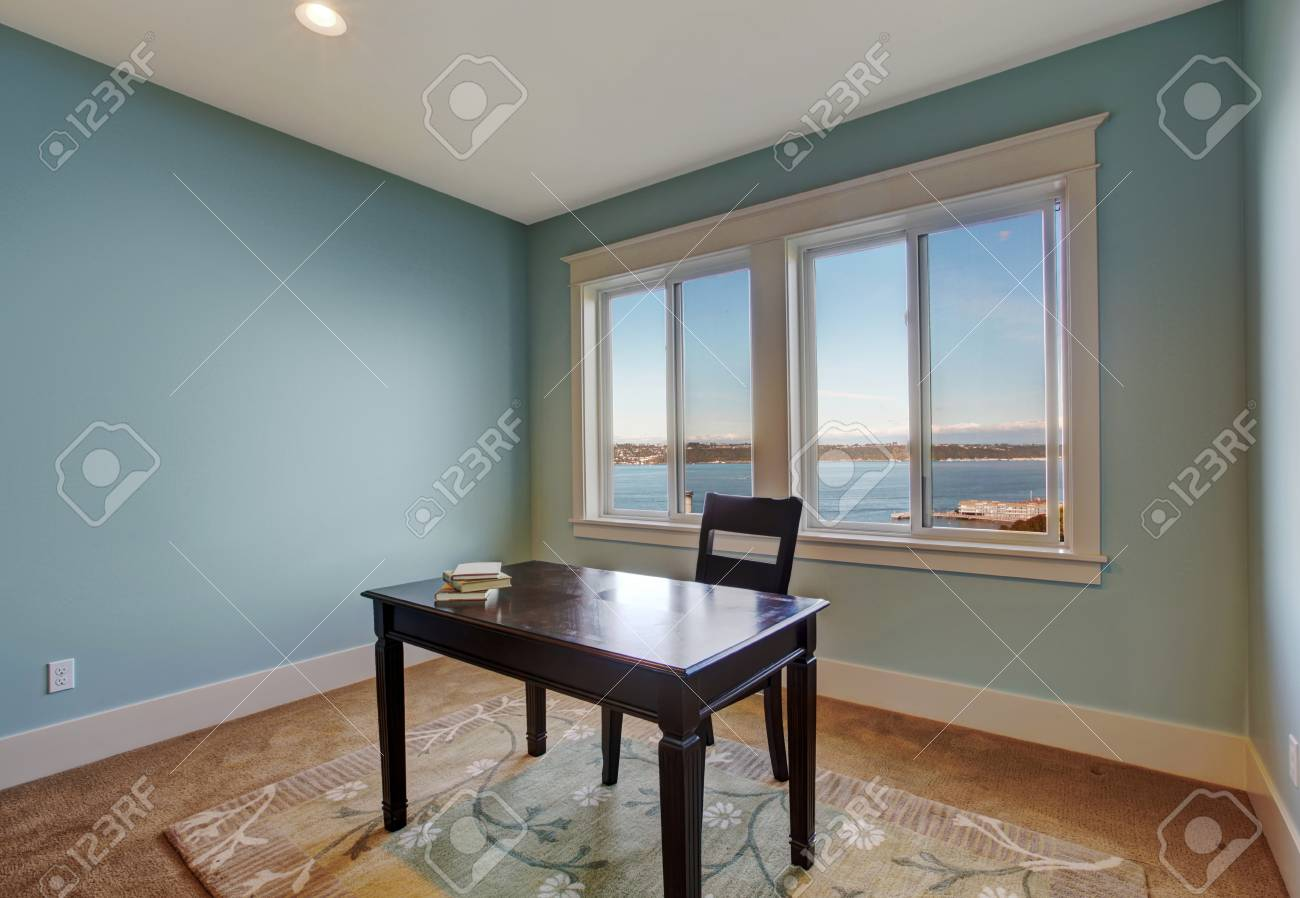 simple office room in light blue color and bay view dark brown desk with chair