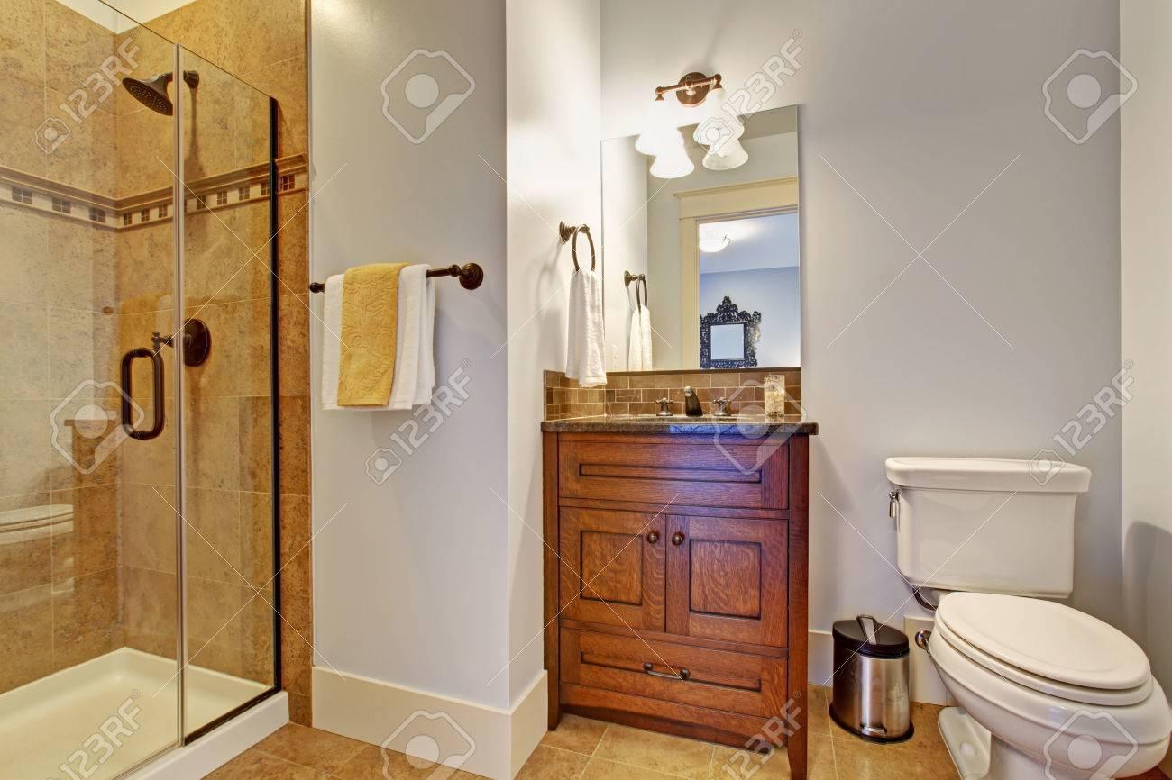 Intérieur de salle de bain chaud avec meuble de rangement en bois et porte  en verre douche avec garniture de mur de carreaux