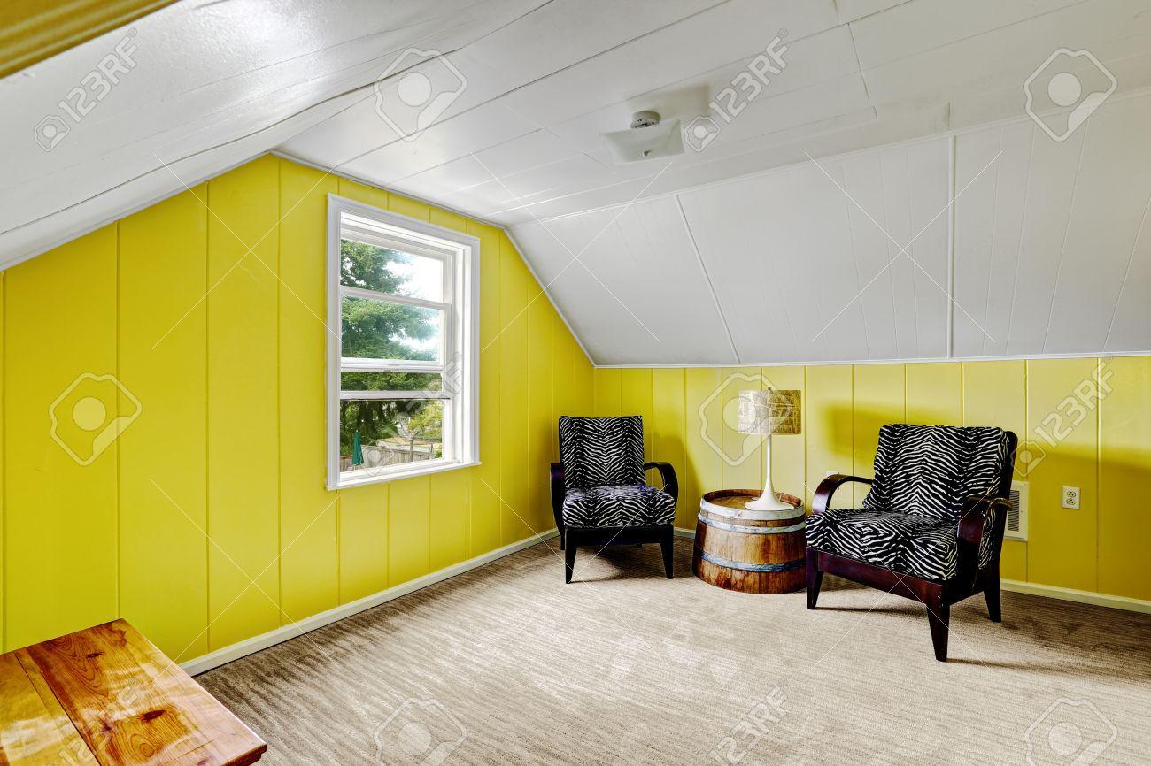 Chambre jaune clair avec du blanc plafond voûté. Coin salon avec deux  chaises noires et une table décorative