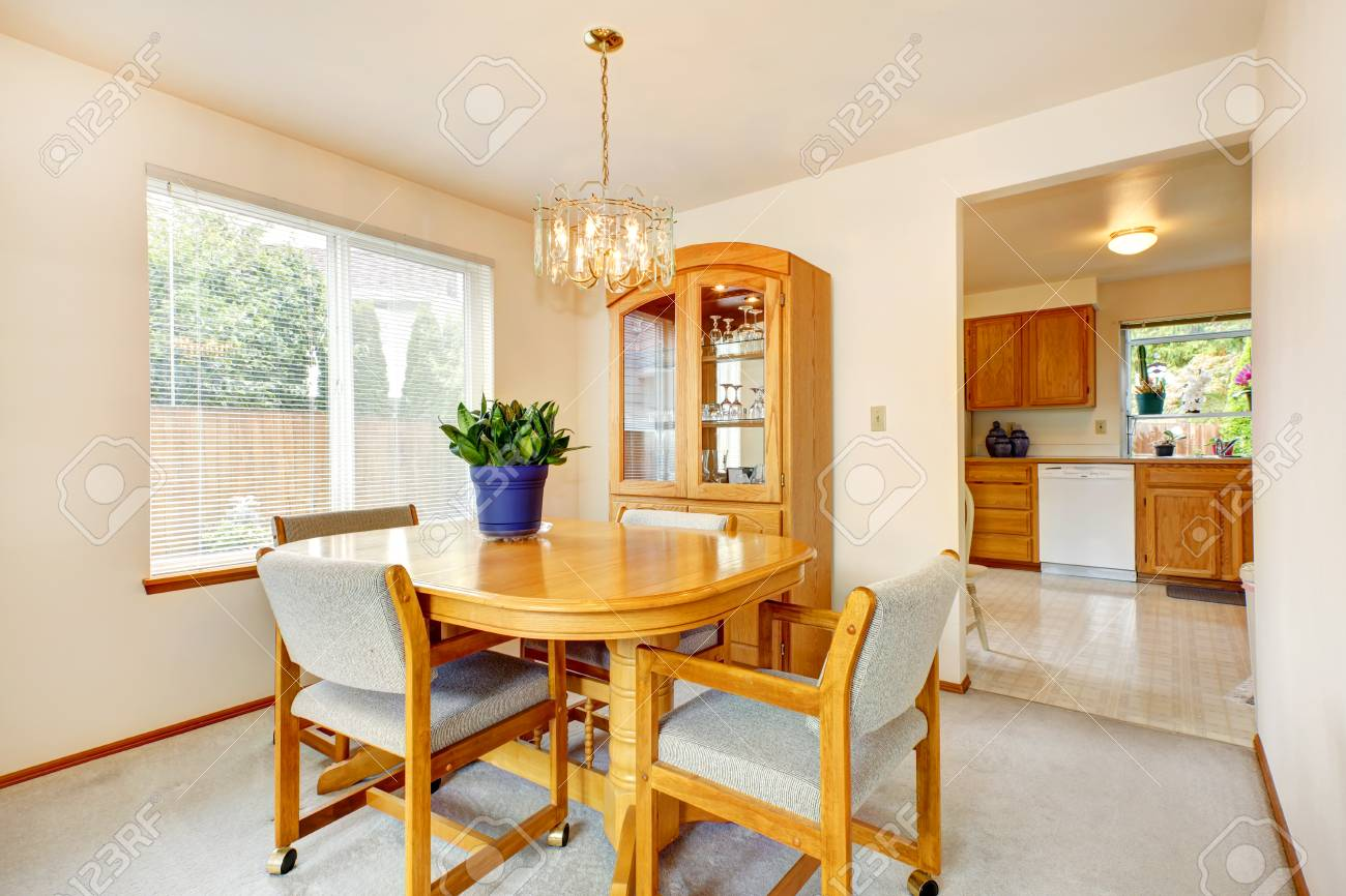 Bright dining area with maple dining table set and storage cabinet with glass door Stock Photo & Bright Dining Area With Maple Dining Table Set And Storage Cabinet ...