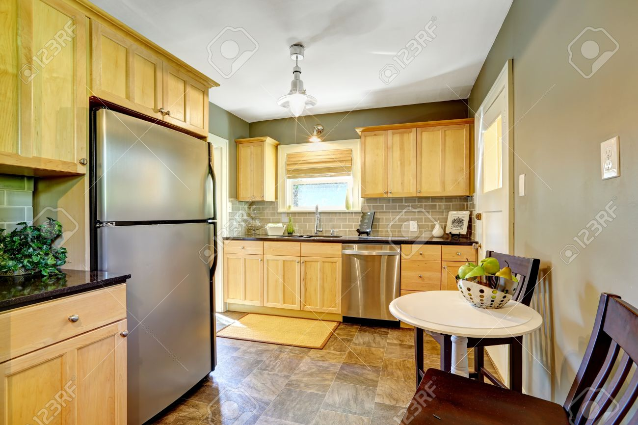 Small kitchen room with maple storage cabinet, steel dishwasher..