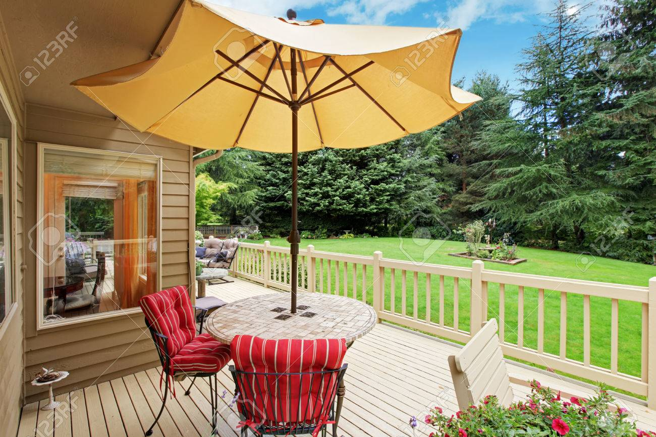 Holz Ausstand Terrasse Mit Gartentisch, Sonnenschirm Und Stühlen Mit Blick  Auf Hinterhof Landschaft Standard