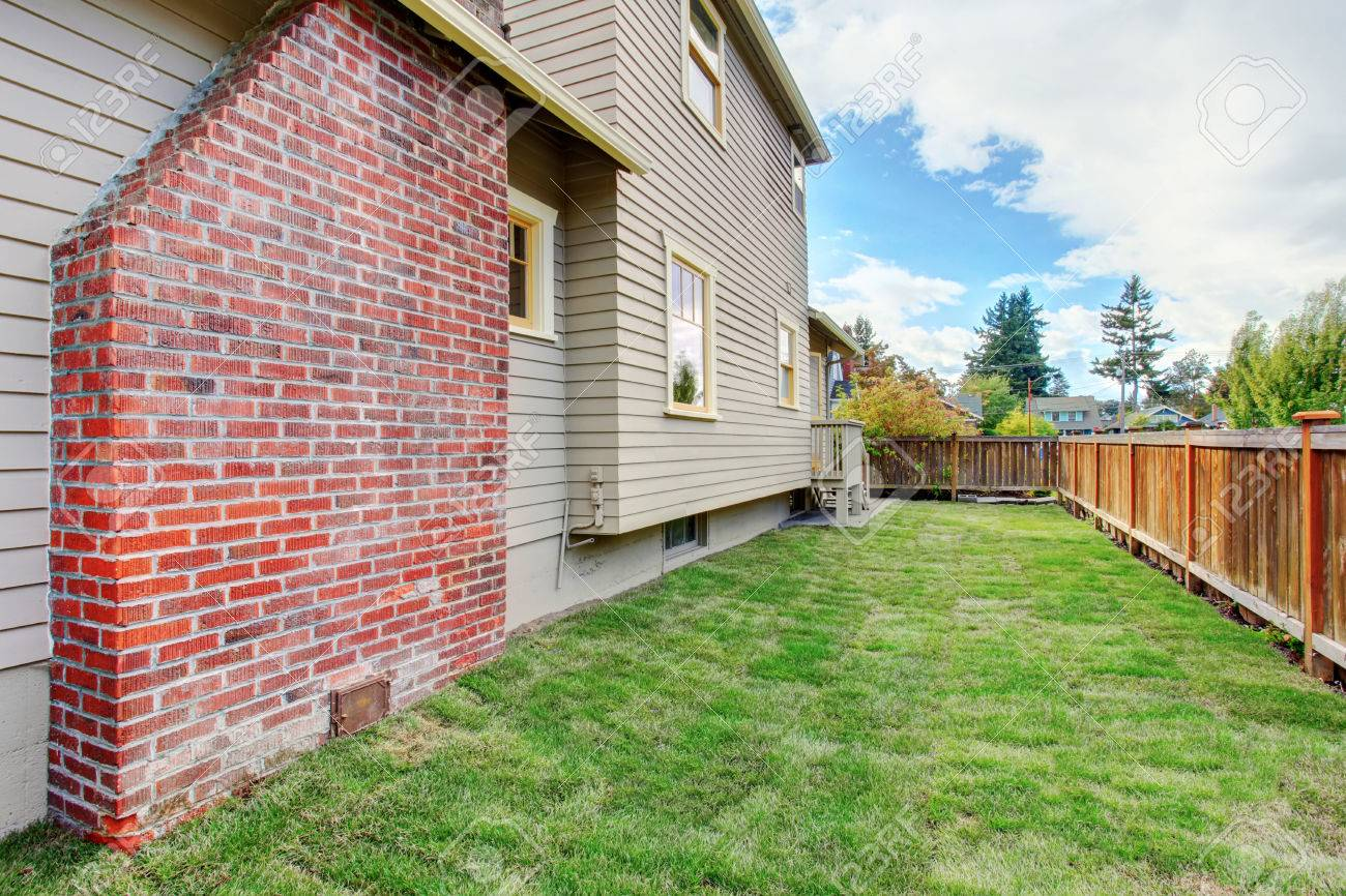 house exterior with brick chimney fenced empty backyard with