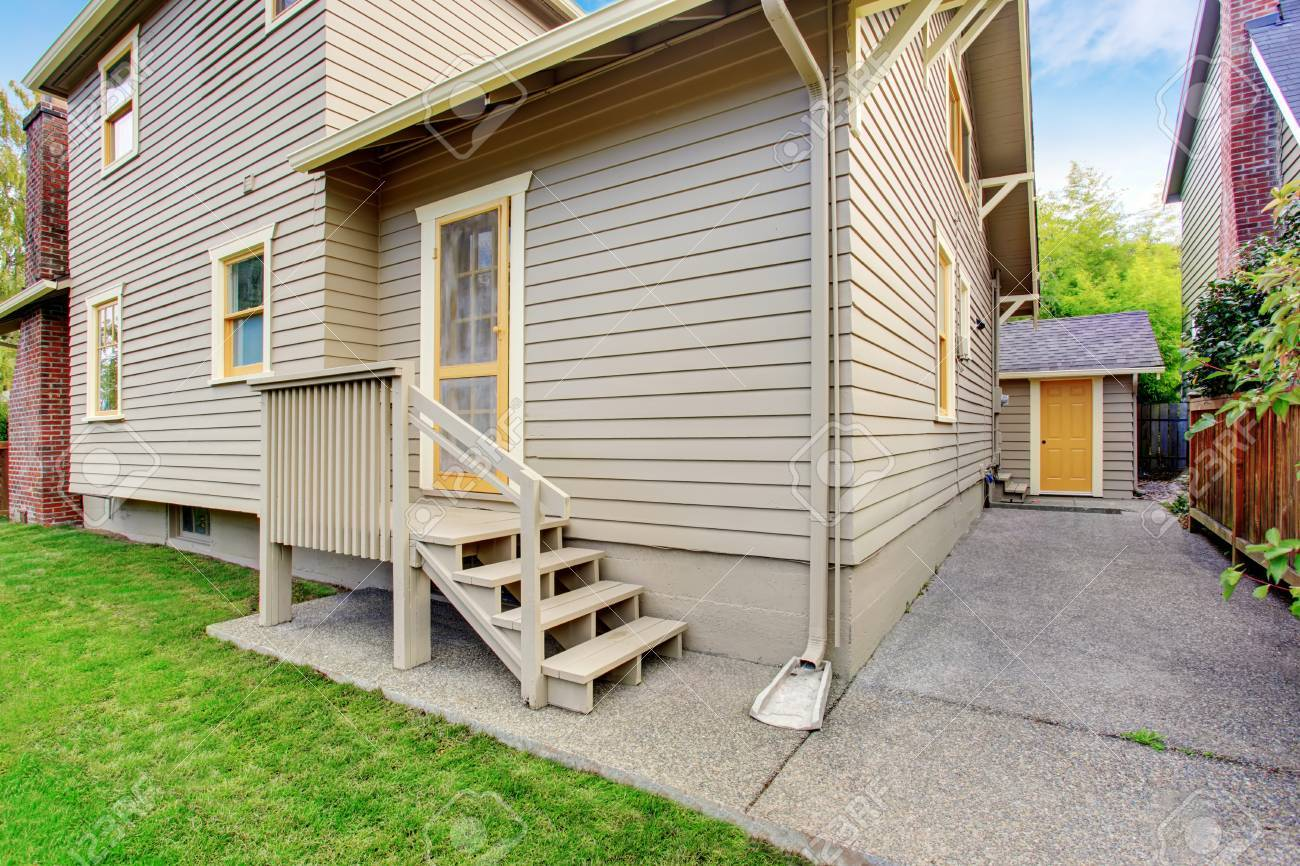 house with small deck and concrete walkways backyard view stock