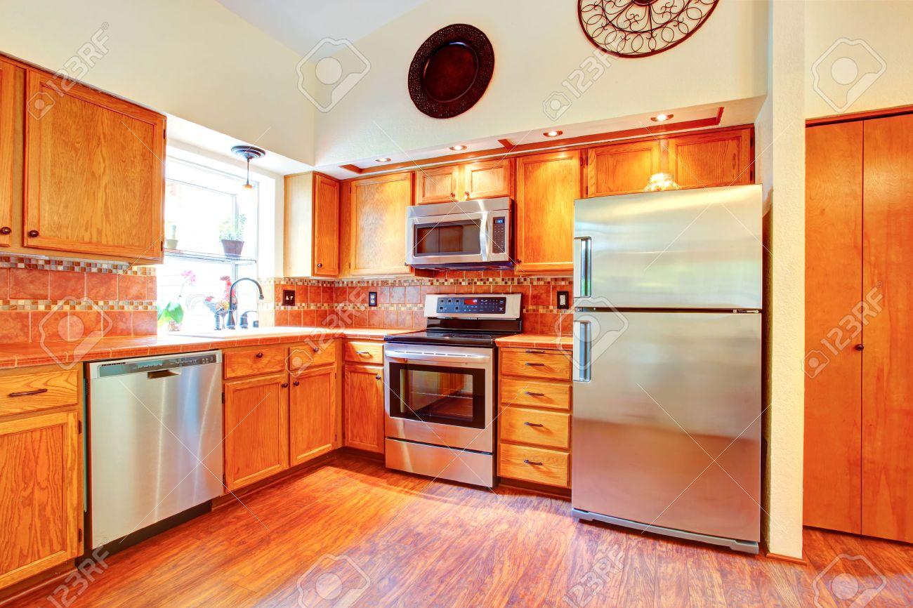 Kitchen room with orange tile back splash trim, maple cabinets..