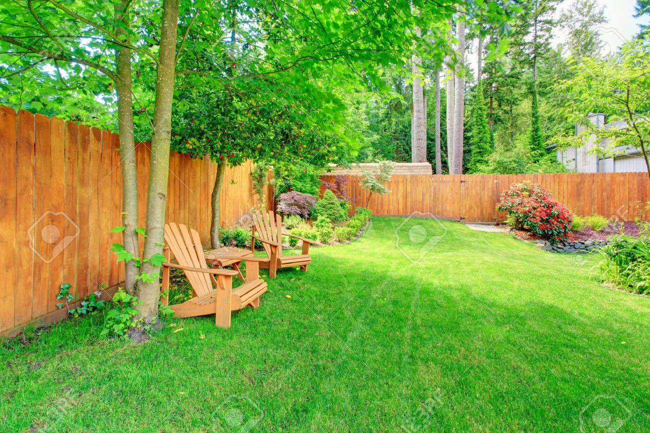 Delicieux Fenced Backyard With Green Lawn, Flower Beds And Romantic Sitting Area With  Wooden Chairs And
