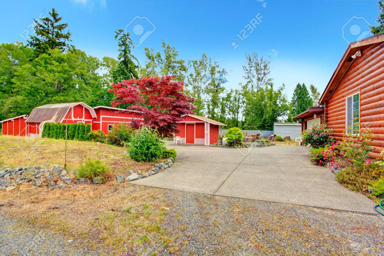 log cabin style house exterior with farm sheds in bright red