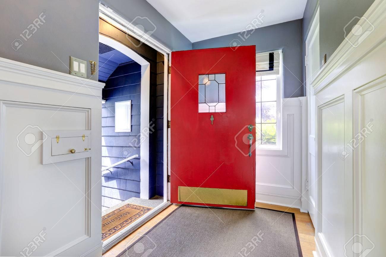Eingangshalle mit holzboden, weiße und graue wände und helle rote ...