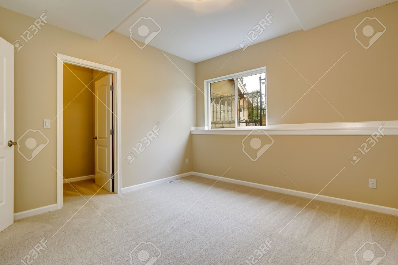 Bright Empty Bedroom In Light Ivory Tone With Carpet Floor And Small Window Room