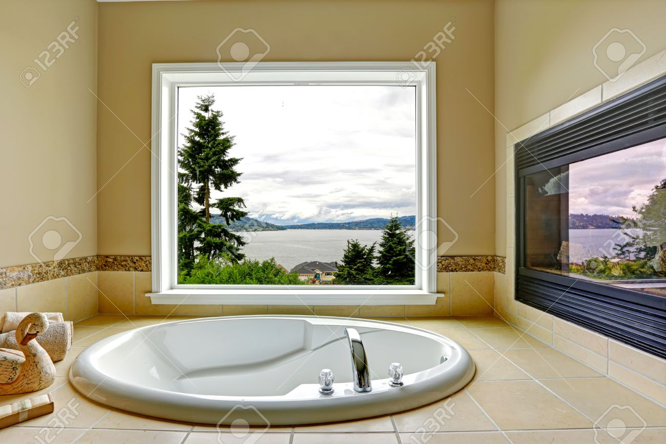 Luxury Bathroom With Fireplace And Bay View. White Bath Tub With ...