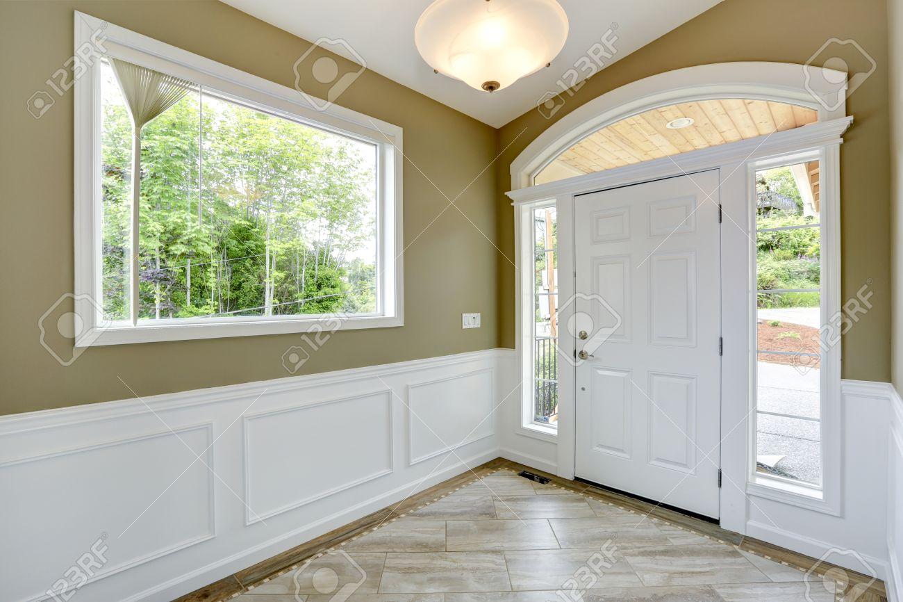 Hal met tegelvloer en beige muur met witte versiering. witte deur ...