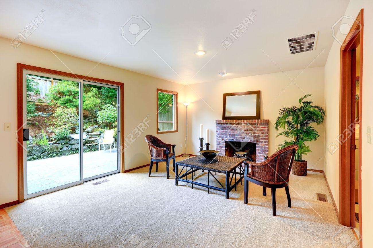 Living Room With Sitting Area By The Fireplace With Wicker Chairs