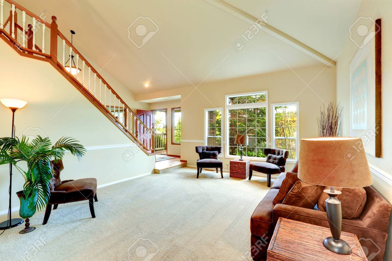 Bright ivory living room with high vaulted ceiling and french..