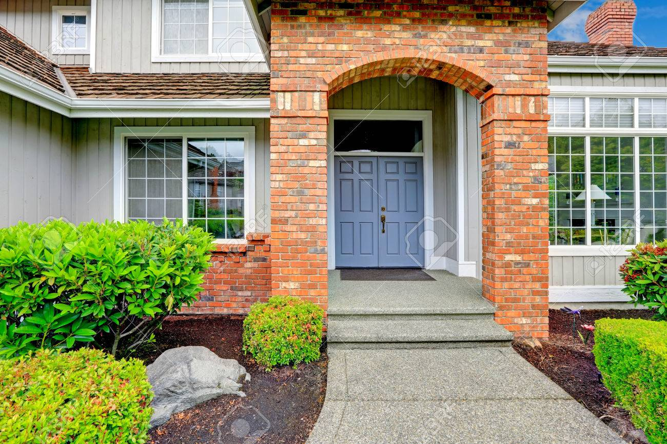 House Exterior. Entrance Porch With Brick Trim, And Large French Windows  Stock Photo