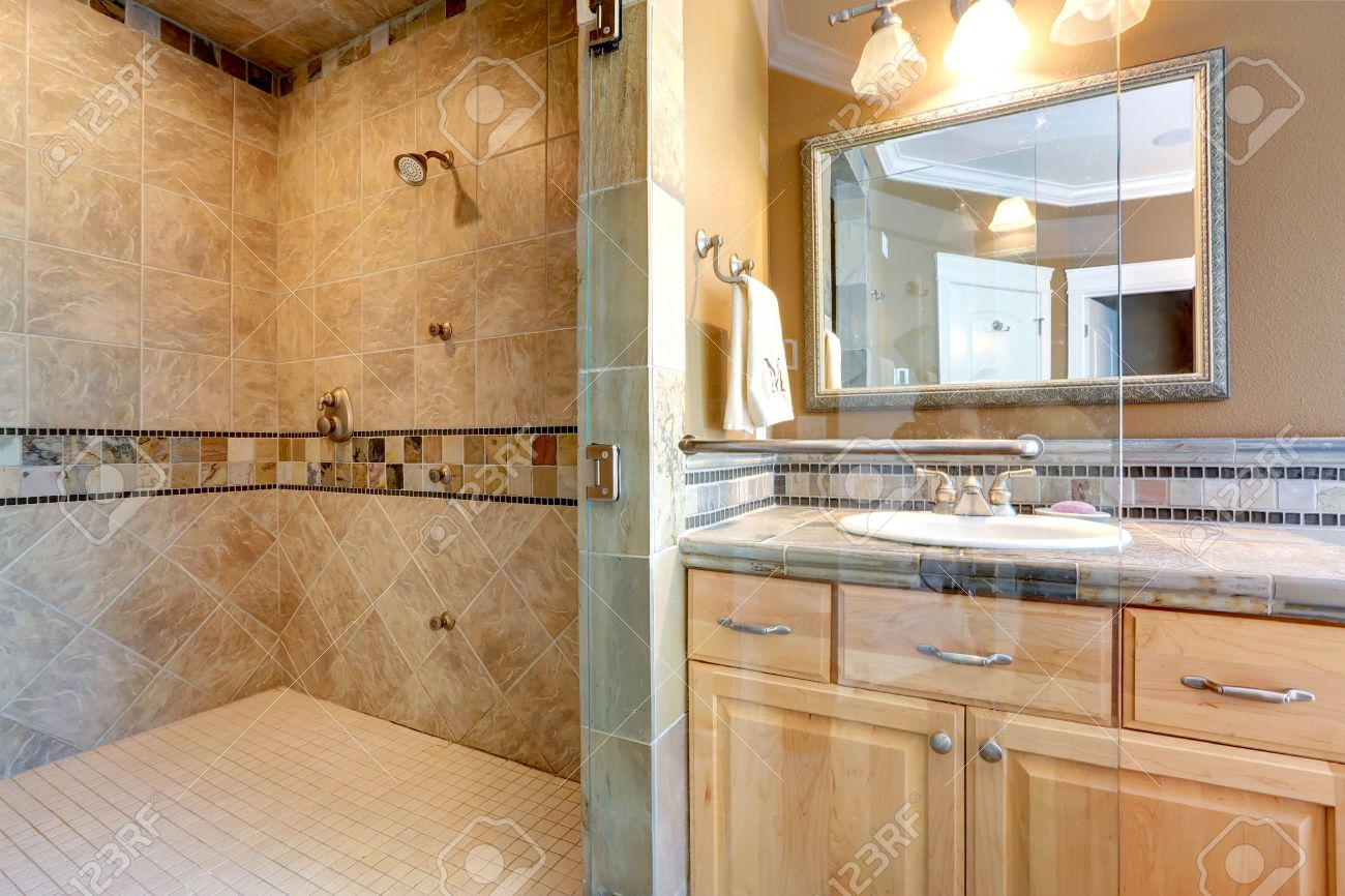 luxury bathroom interior with tile wall trim, open shower and