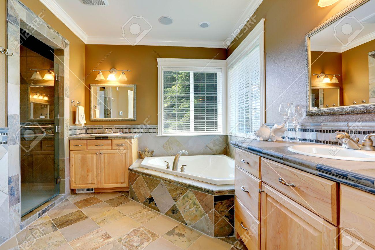 luxus-badezimmer interieur in senf farbe mit eckbadewanne und zwei