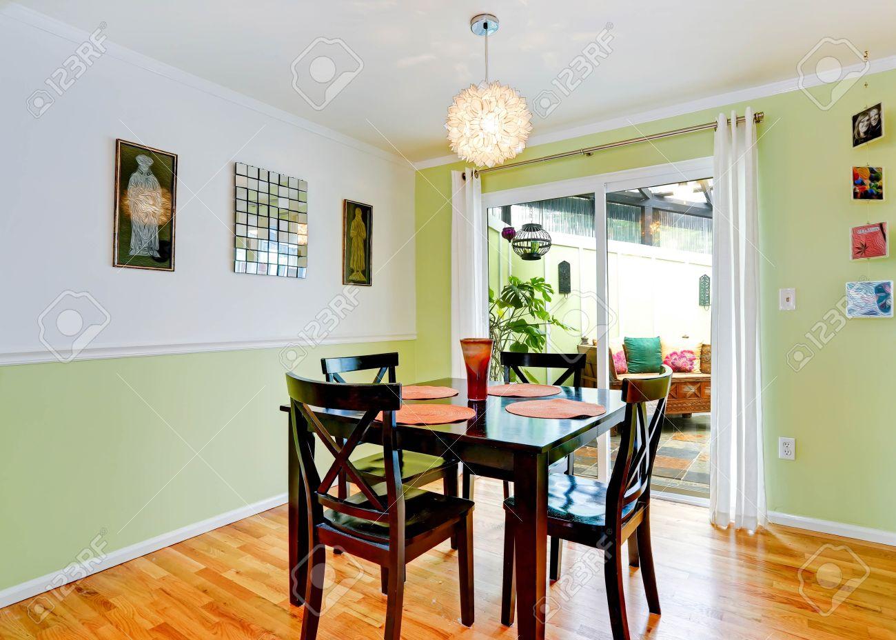 Acogedor comedor con blanco y menta paredes de color marrón oscuro con el  conjunto mesa de comedor. La habitación tiene salida al patio trasero