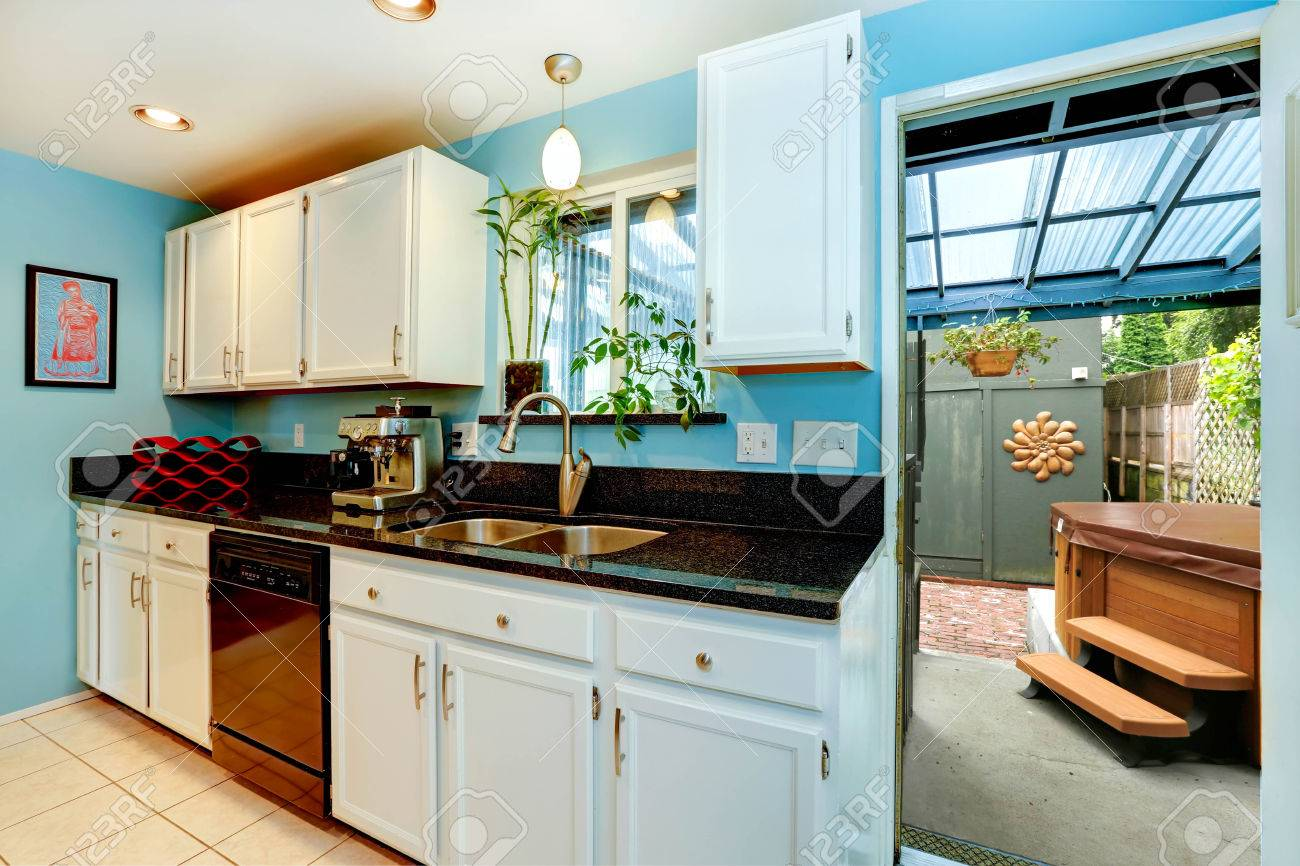 Light blue kitchen room with white cabinets and black counter..