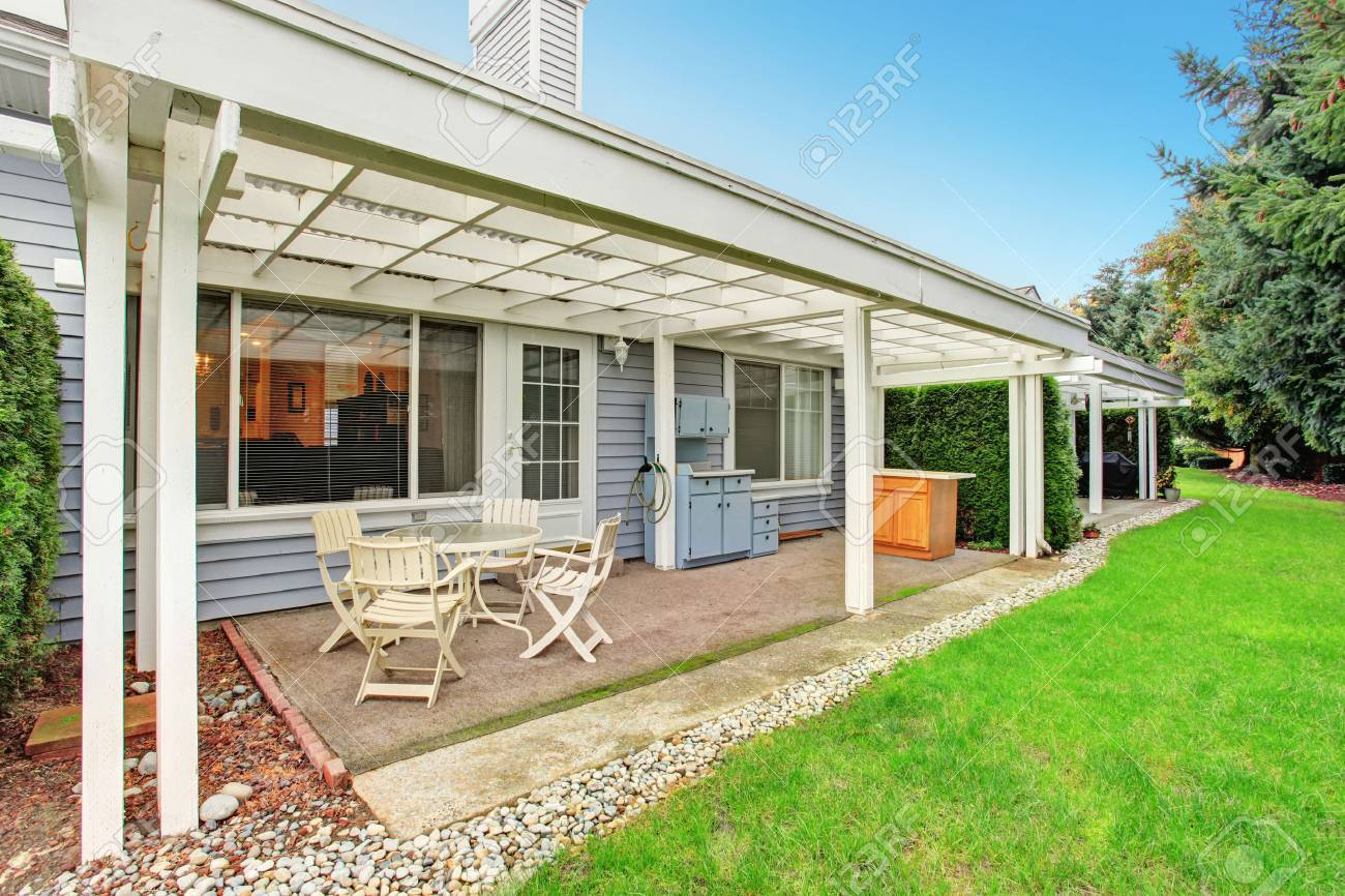 Simple covered back patio with cabinets, chairs, and a table. Stock Photo - - Simple Covered Back Patio With Cabinets, Chairs, And A Table. Stock
