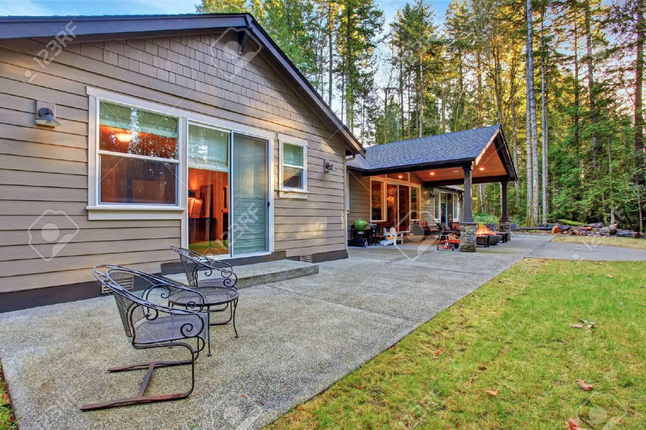 Grande cour arrière avec de l\'herbe et terrasse couverte avec foyer.