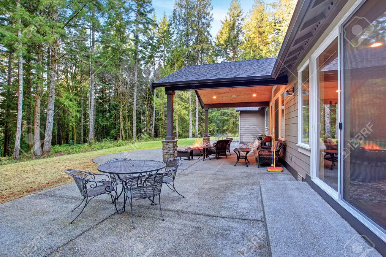 großen hinterhof mit gras und überdachte terrasse mit feuerstelle