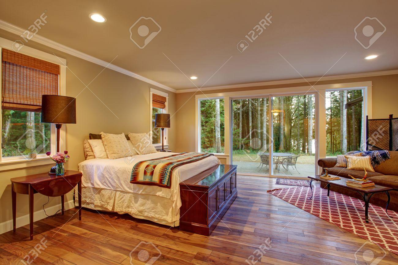 Grande chambre des maîtres avec plancher de bois franc et porte coulissante  en verre à l\'arrière.