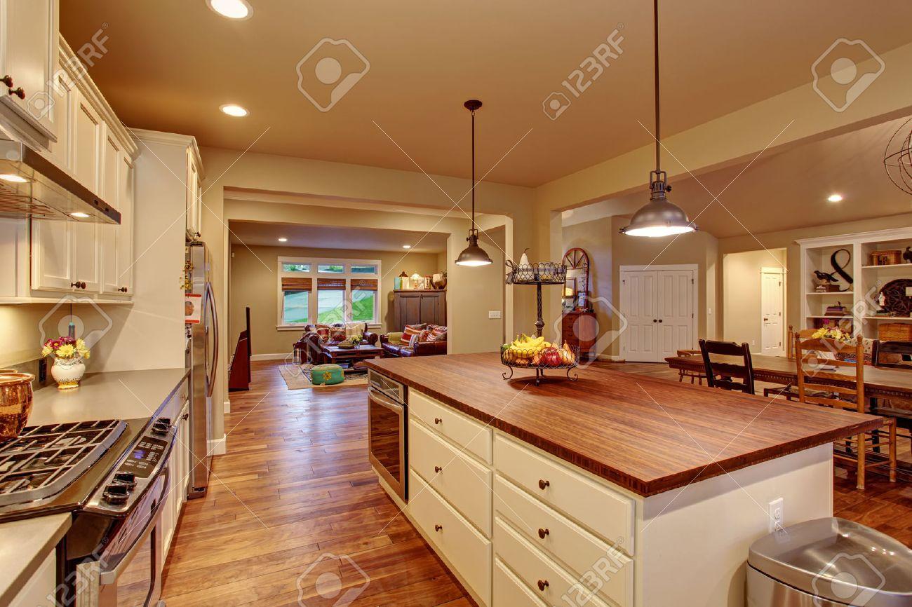 Cocina clásica con suelo de madera, una isla, y comedor conectado y sala de  estar.