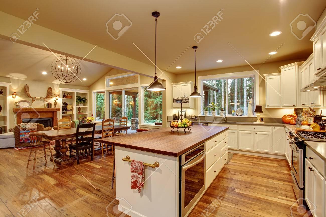 Cocina clásica con suelo de madera, una isla, y comedor conectado.