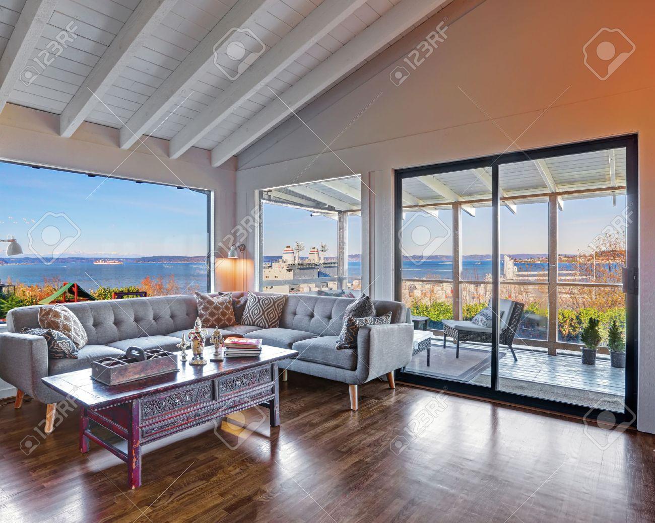 Vardagsrum hörn med stor grå soffa, vackra trägolv och välvda tak ...